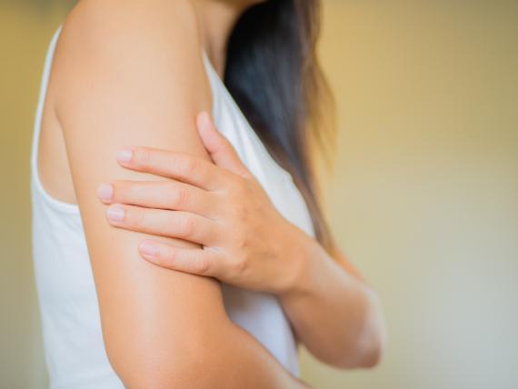 Una mujer se toca el brazo con la mano