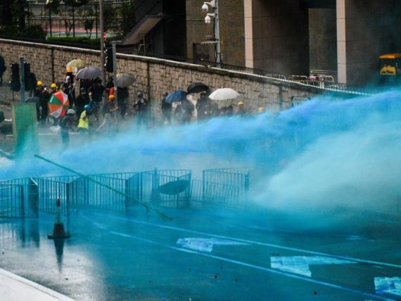Los cañones de agua colorean con spray azul a los manifestantes.