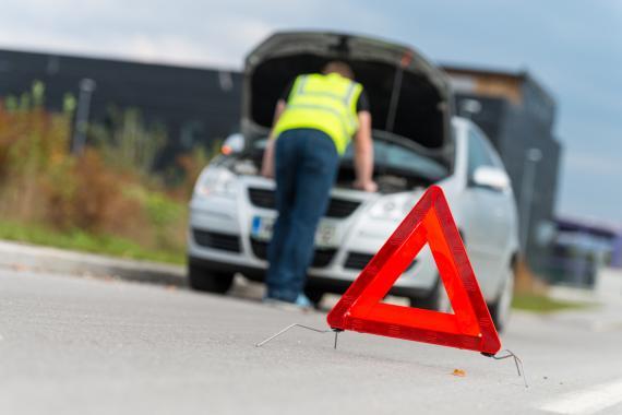 Un hombre con un chaleco inspecciona el interior de un coche detrás de un triángulo de preseñalización