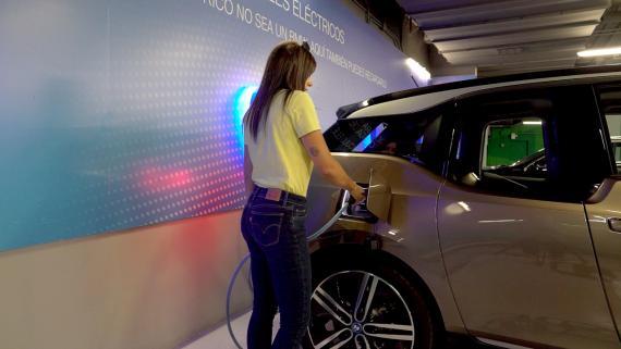 Una mujer recarga eléctricamente un BMW i3.