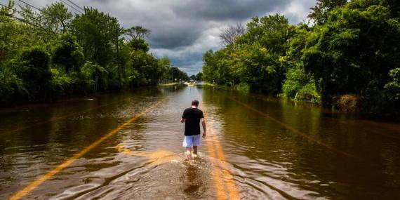 Un hombre camina por una carretera inundada en Islip, Nueva York en 2014.