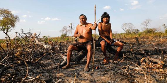 Los miembros de la tribu Xavante se sientan en ramas carbonizadas en la selva amazónica.
