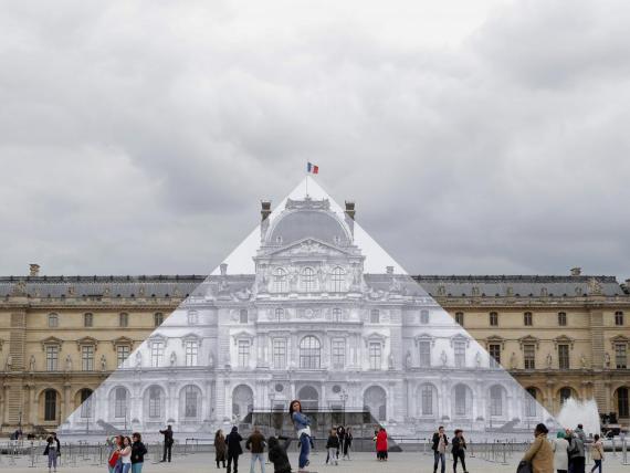 Los turistas caminan alrededor del proyecto JR en el Louvre en París, Francia, en 2016.