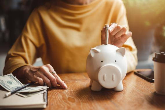 Señora metiendo dinero en una hucha
