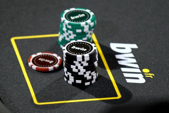 Unas fichas de poker en una mesa con publicidad de Bwin
