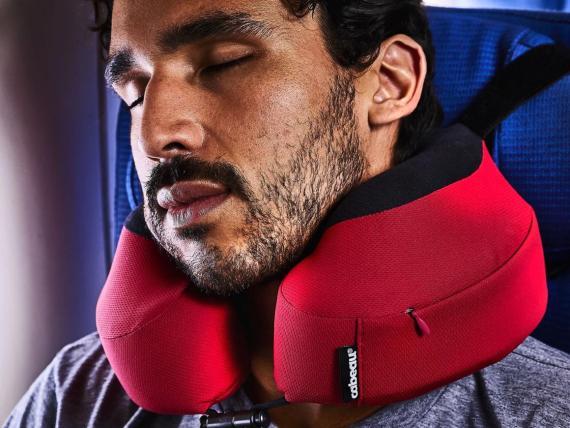 Esta almohada de viaje de 50 euros se adhiere a tu reposacabezas, así que puedo dormir en un avión, incluso en el asiento central.