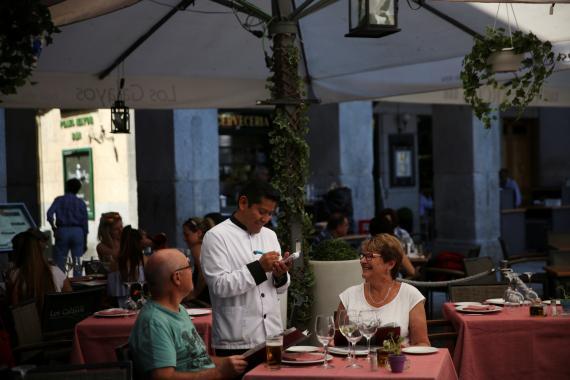Un camarero atiende a una pareja de turistas en una terraza de Málaga