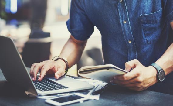 Hombre con un libro y un ordenador