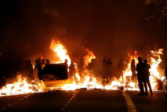Un grupo de manifestantes quema varios contenedores en medio de la calzada en el centro de Barcelona durante las protestas contra la sentencia del procés.