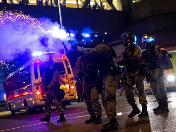 Un policía antidisturbios dispara una lata de gas lacrimógeno contra manifestantes antigubernamentales en Hong Kong.