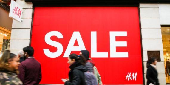 Los consumidores caminan delante de un escaparate de H&M con el cartel de rebajas en Oxford Street en Londres.