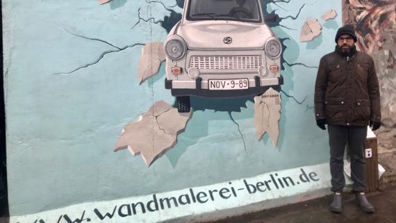 El autor de esta crónica posa delante del Muro de Berlín donde aparece un icónico Trabant.