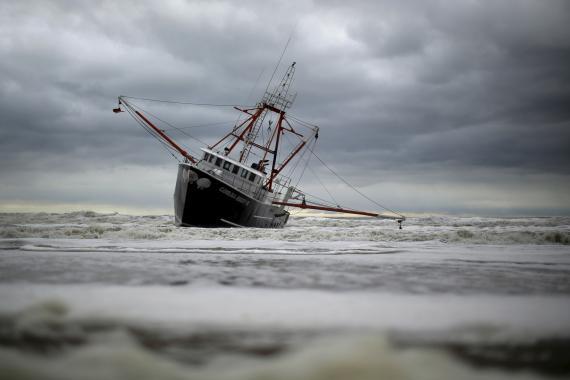 Un barco escorado junto a la playa