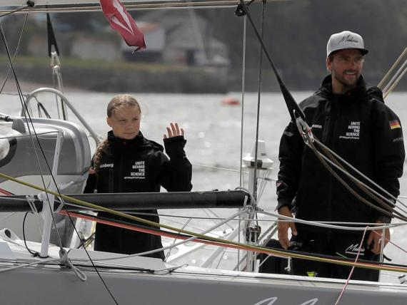 Climate change activist Greta Thunberg and skipper Boris Herrmann wave from the Malizia II boat in Plymouth, England, Wednesday, Aug. 14, 2019. She'll sail back across the Atlantic to hopefully reach COP25, which starts on December 2.