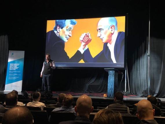 El fundador de FINOS. Gabriele Columbo, habla frente a un dibujo de Jamie Dimon y Jeff Bezos.