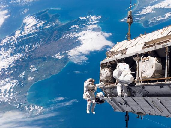 Backdropped by New Zealand and the Cook Strait in the Pacific Ocean, astronauts Robert L. Curbeam Jr. (left) and Christer Fuglesang (right) participate in an extravehicular activity (EVA).
