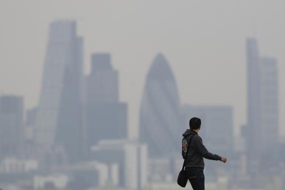 Un turista pasea con el skyline de Londres de fondo durante un fuerte episodio de contaminación en la capital británica.