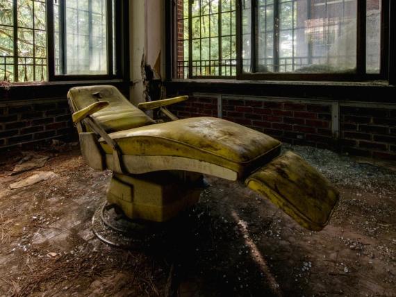 Espeluznante silla de paciente dentro de un hospital psiquiátrico abandonado.