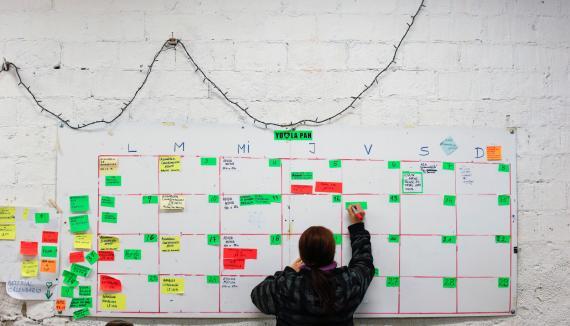 Un activista de la PAH anota actividades en un calendario mural
