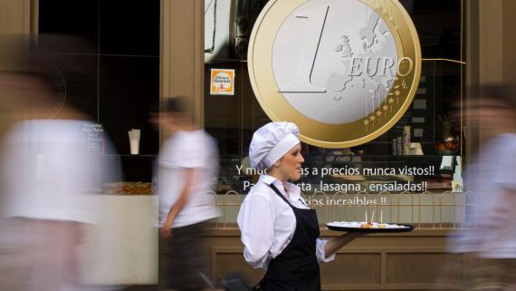 Una camarera ofrece pinchos a los viandantes a la puerta de un restaurante de Madrid