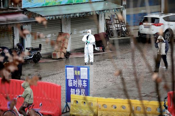 Un trabajador con un traje protector inspecciona las inmediaciones del mercado de marisco de Wuhan, epicentro del coronavirus.