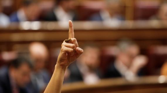 Una diputada levanta la mano en el Congreso de los Diputados para marcar el sentido de voto a sus compañeros de partido