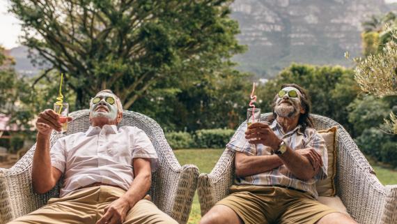 Dos hombres adultos, casi jubilados, relajados tomando un te mientras tienen una mascarilla en la cara