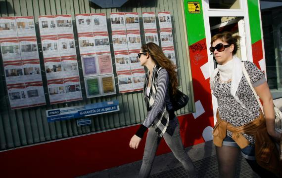 Dos jóvenes pasan ante los anuncios de pisos en la fachada de una inmobiliaria en Madrid