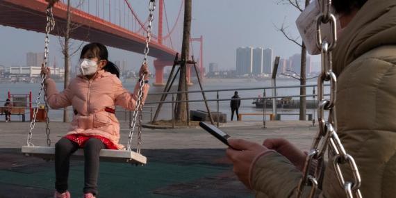 Una niña juega en un columpio cerca del puente del río Yingwuzhou Yangtze en Wuhan.