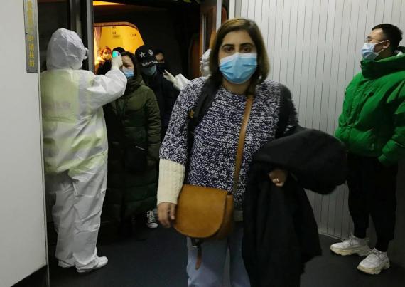 Personal sanitario con equipo de protección comprueba las temperaturas de los pasajeros que llegan al aeropuerto de Pekín desde Wuhan, China, el pasado miércoles.