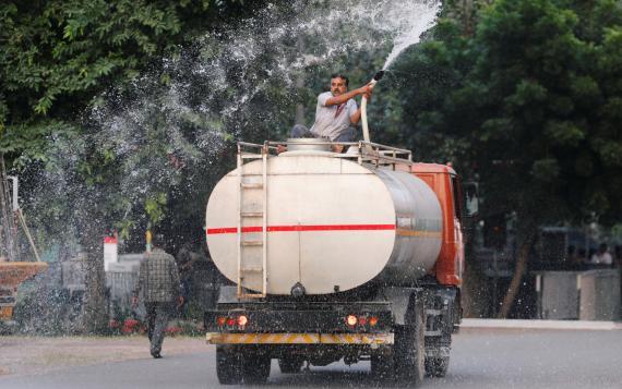 Un hombre rocía agua, mezclada con un reactivo ecológicamente seguro en Nueva Delhi