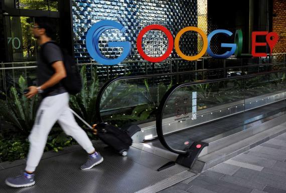 Un hombre junto a un cartel de Google en sus oficinas de Singapur.