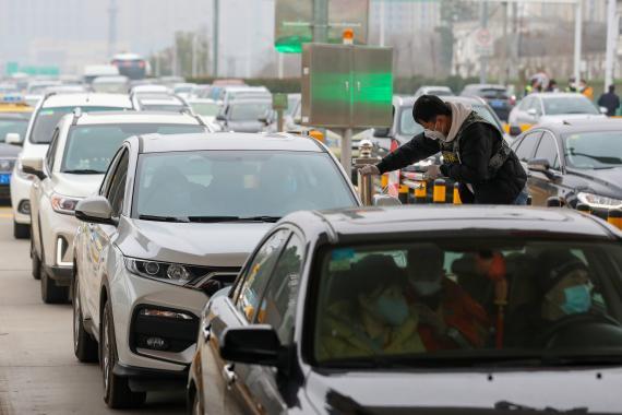 Un operario lleva a cabo controles térmicos a los conductores y pasajeros de vehículos en Wuhan, epicentro del coronavirus.