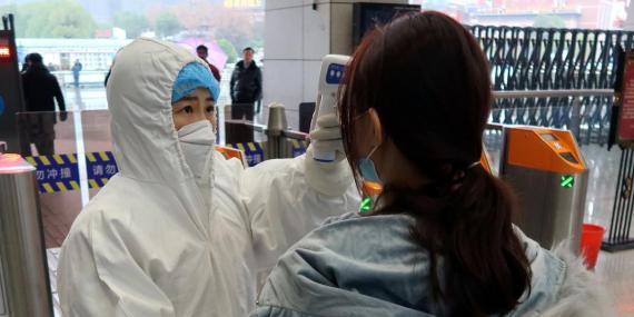 Un trabajador con traje protector controla la temperatura de pasajeros antes de entrar a una estación de Wuhan el 24 de enero de 2020.