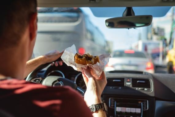 Hombre comiendo mientras conduce.