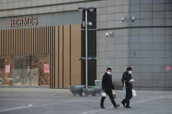 Dos ciudadanos de origen chino caminan con mascarillas delante de la tienda de la marca de lujo de Hermés en el distrito financiero de Pekín.