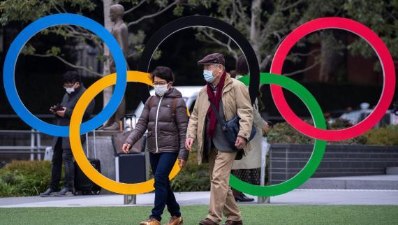 Dos personas caminan frente al logo de los Juegos Olímpicos en Tokio.