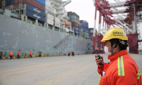 Un estibador controla la descarga de un carguero comercial en el puerto chino de Qingdao