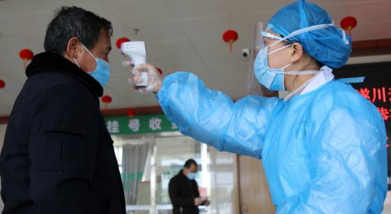 Una funcionaria toma la temperatura a un hombre a la entrada de un edificio público en Sichuan (China)
