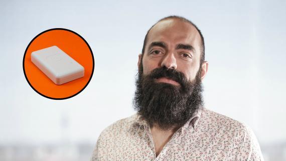 El fundador y CEO de ElParking, Enrique Domínguez, junto a una imagen del dispositivo.