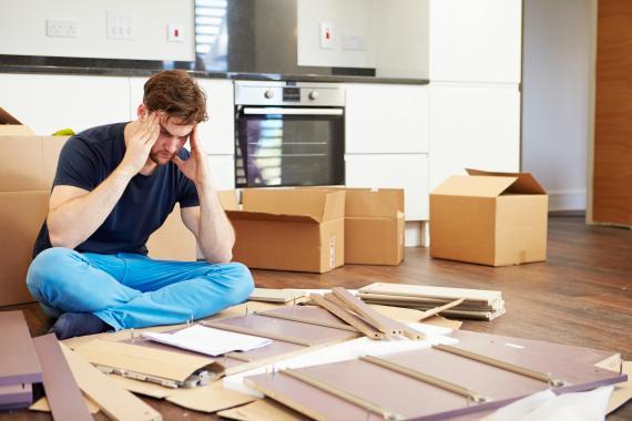 Hombre frustrado intentando montar un mueble