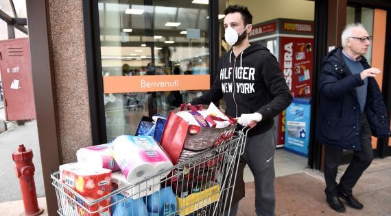 Un hombre sale de un supermercado en Italia cargado de productos básicos