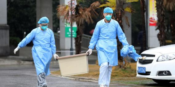 Medical staff carry a box by the Jinyintan hospital in Wuhan, which houses patients with the Wuhan coronavirus, on January 10, 2020.