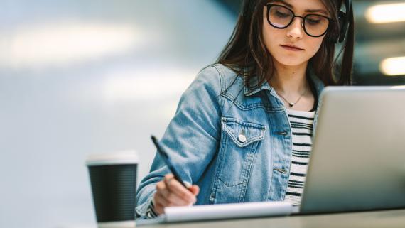 Una mujer escribe notas delante de la pantalla de un ordenador