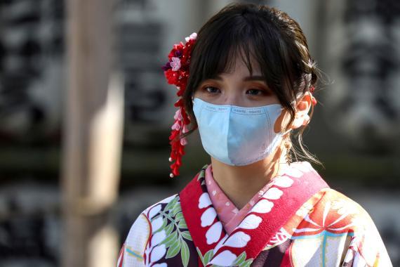 Una mujer pasea con una mascarilla por Tokio para protegerse durante el brote del coronavirus de Wuhan
