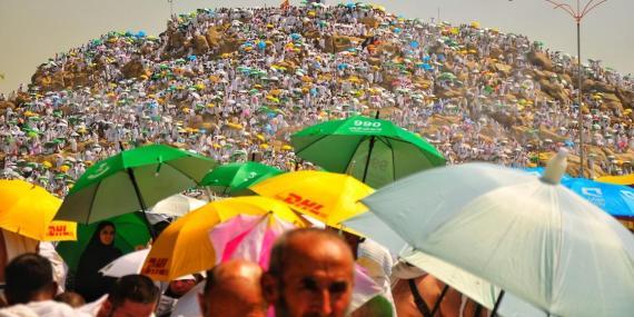 Peregrinos musulmanes llevando paraguas para protegerse del sol.
