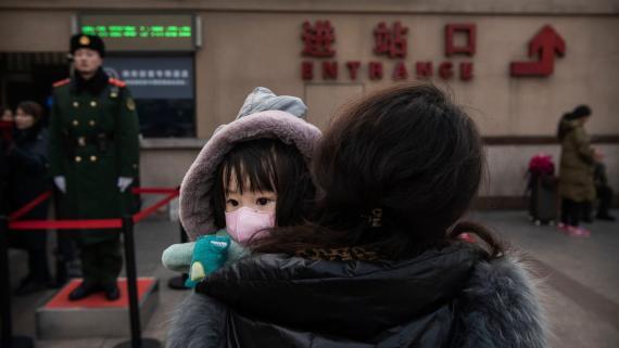 Una niña lleva una máscara en la estación central de trenes de Pekín.
