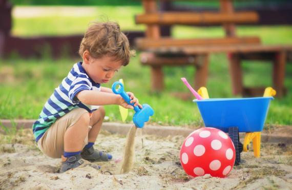 Un niño juega en un cajón de arena, sandbox.