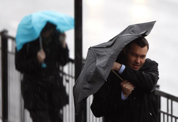 Persona tapándose con un paraguas ante la tormenta