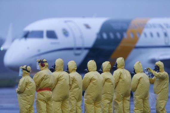 Soldados con trajes protectores esperan a pasajeros repatriados desde Wuhan, China.